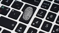 An image of a fingerprint on the enter key of a keyboard
