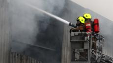 An image of two firefighters in a cherry picker hosing a blaze at a factory in Broxburn in West Lothian