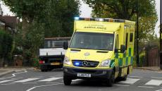 An image of a London ambulance driving down a residential street