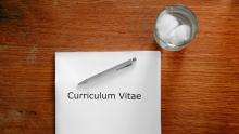 Image of a CV on a table with a glass of water
