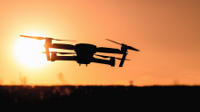 Image of a drone flying against the backdrop of a sunset