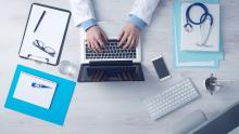 A top-down image of a doctor sitting at a desk and using a computer