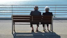 Image of an elderly couple sat on a bench looking out to sea