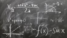 An image of some equations written on a blackboard