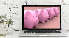An image of a laptop with a row of piggy banks displayed onscreen