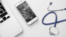 A close-up image of a laptop, a phone, and a stethoscope lying next to each other on a white surface