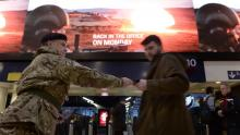 An image of an army reservist handing out a recruitment leaflet to a commuter
