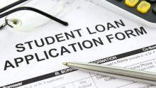 An image of a piece of paper headed 'student loan application form' with a pen resting on top