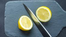 An image of a lemon that has just been cut in half by a kitchen knife
