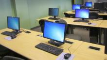 An image of computers on desks in an empty classroom