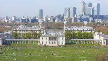 An image of Greenwich Park with the Canary Wharf skyline in the background