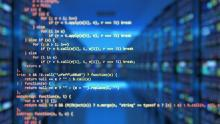 An image of computer code superimposed on a blurred image of a datacentre