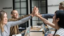 An image of four co-workers sitting round a desk in a modern office. They are smiling and conducting a group high five
