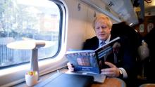 An image of Boris Johnson reading the Conservative manifesto on a train