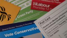 A close-up image of a poll card and party leaflets