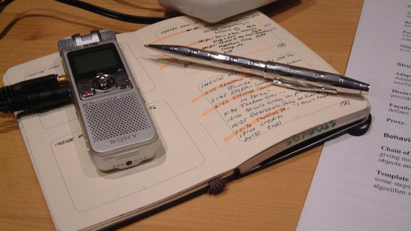 A dictaphone with a paper and pen