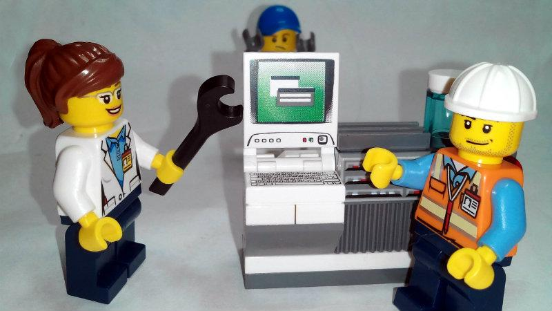 Lego people fixing a computer