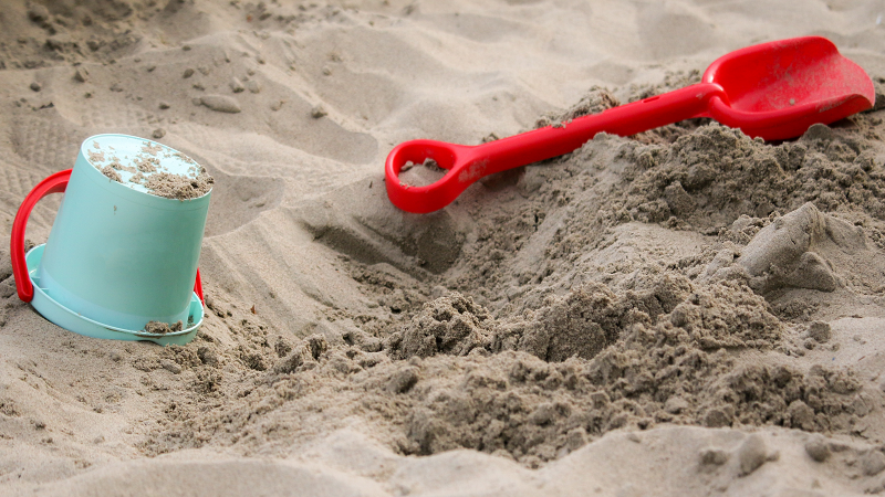 A picture of a bucket and spade in a sand pit