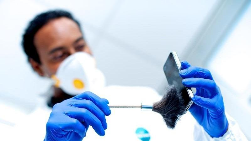 An image of a forensic investigator gathering fingerprints from a mobile phone