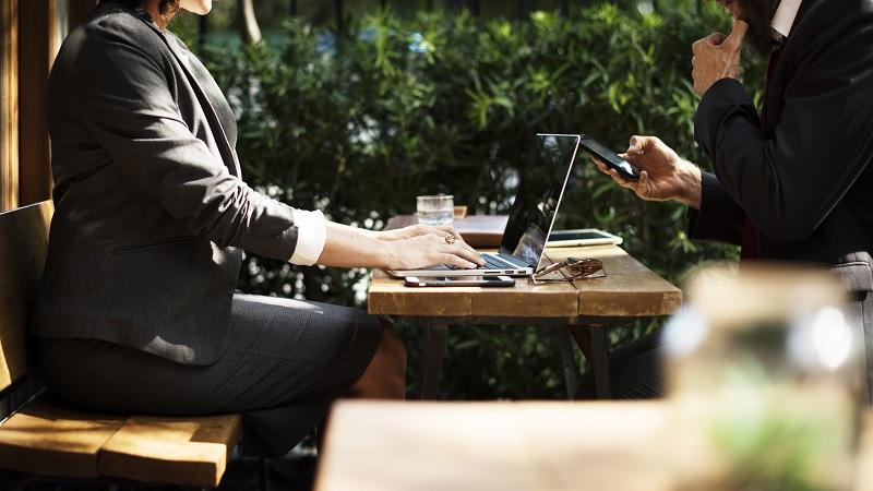 An image of a woman and a man respectively using a laptop and a smartphone in a cafe