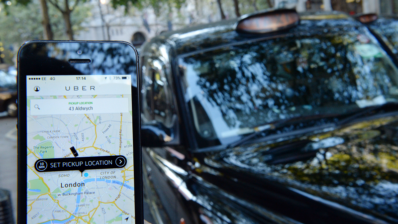 Image of a phone user browsing Uber app in front of a line of black cabs in London
