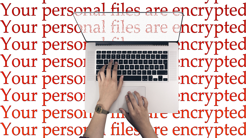 Image of hands using a keyboard with text saying 'your files are encrypted'