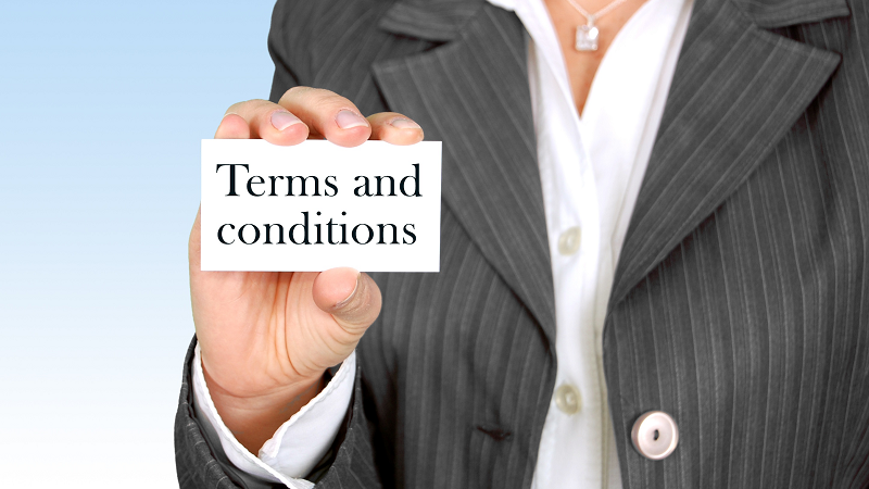 Image of woman holding business card with 'Terms and conditions' printed on it