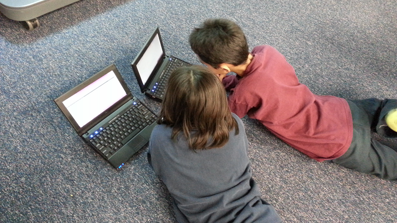 An image of two children each using a laptop