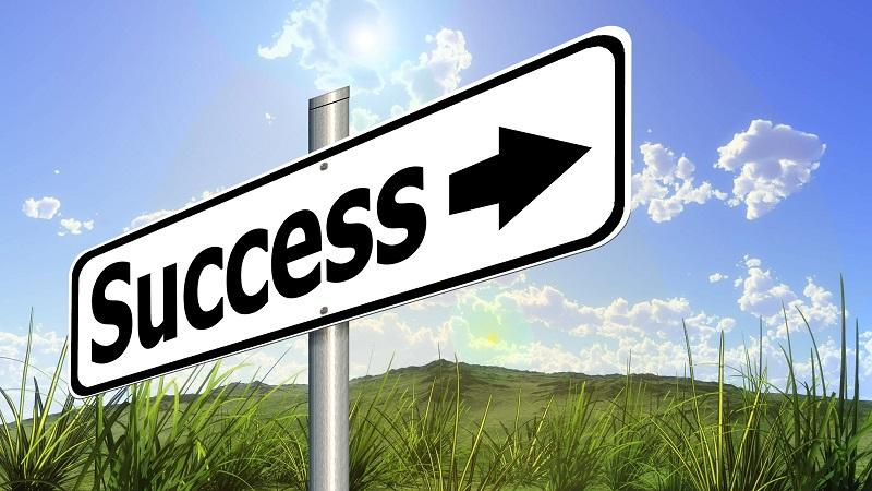 Image of a road sign directing people towards 'success'