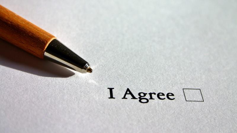 Image of a pen lying next to an 'I agree' tick box