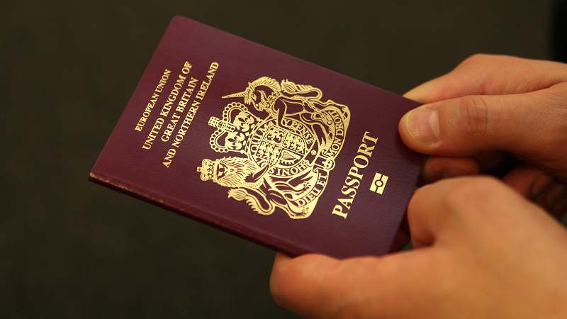 Hands hold UK passport