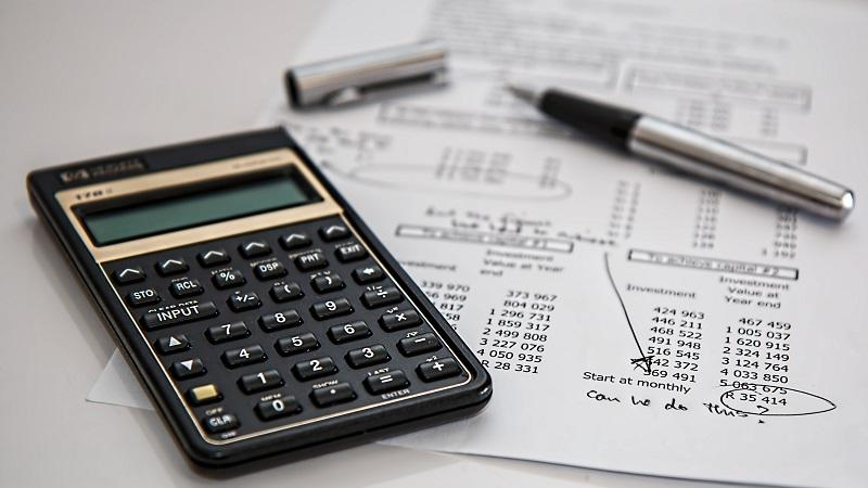 Image of a calculator, a pen and some accounts