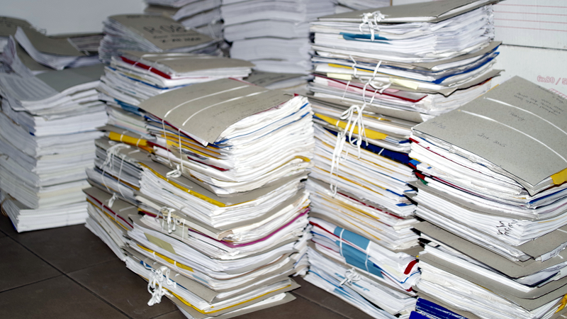 Image of numerous folders of paper stacked up