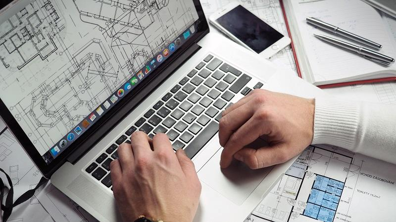 Image of a man's hands using a laptop whose screen displays blueprints for building