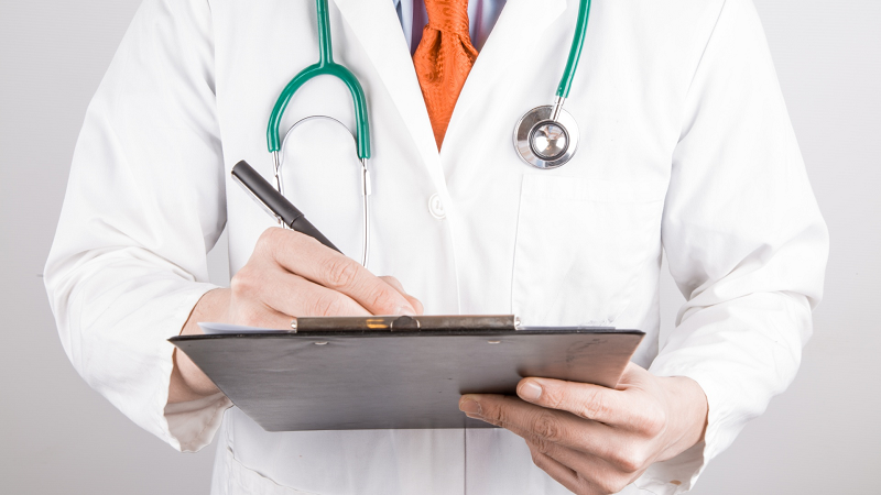 An image of a hospital consultant doctor writing on a clipboard
