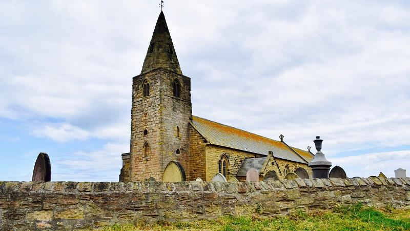 Image of a rural church, with a stone wall and the tops of some gravestones in the foreground