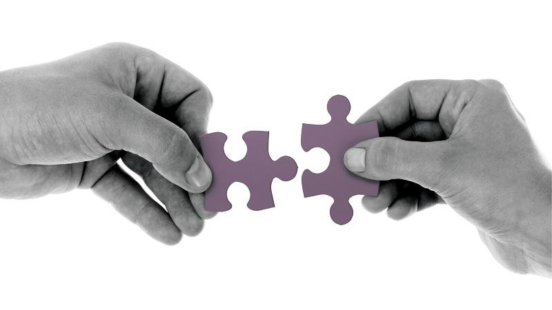 An image of two hands connecting two puzzle pieces