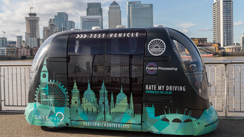 An image of the GATEway Project driverless vehicle pod against the backdrop of the skyline of Greenwich peninsula