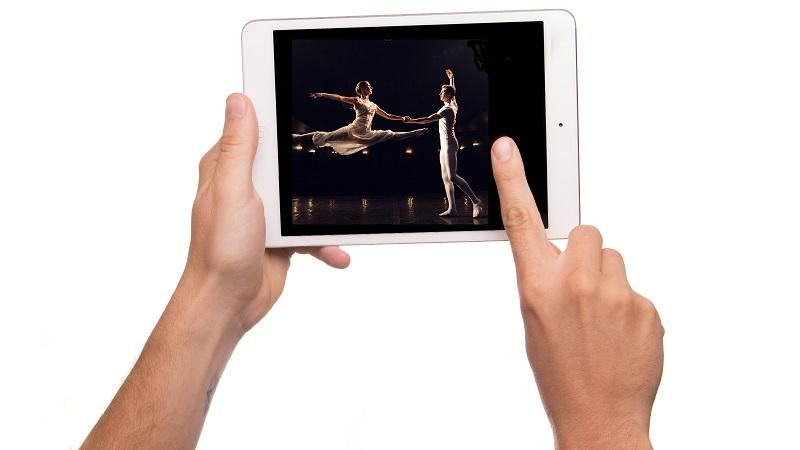 Image of a finger reaching out to touch a tablet screen displaying ballet dancers