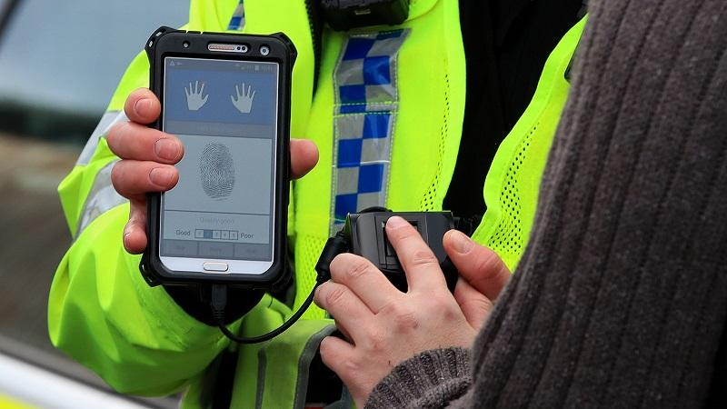 An image of a West Yorkshire Police officer using a mobile fingerprint scanning device