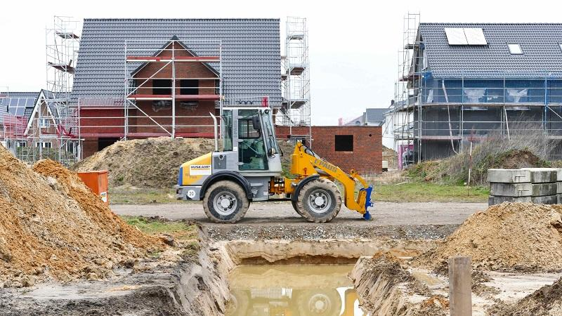 An image of houses under construction with a digger in the middle of the building site