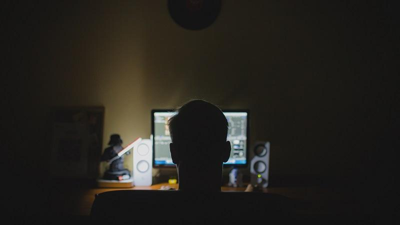 A from-behind image of a man sitting and using a computer in an unlit room