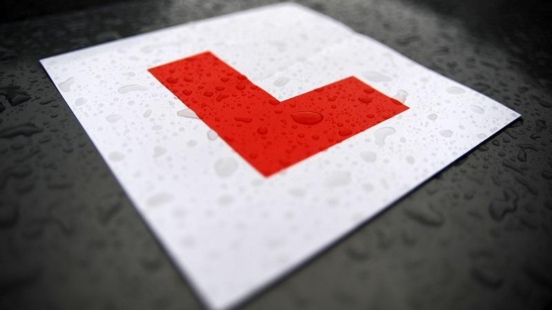 A close-up image of a learner driver's L plate on a rainy day
