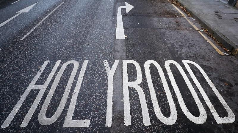 An image of a sign on the road pointing to 'Holyrood' at the next right turn