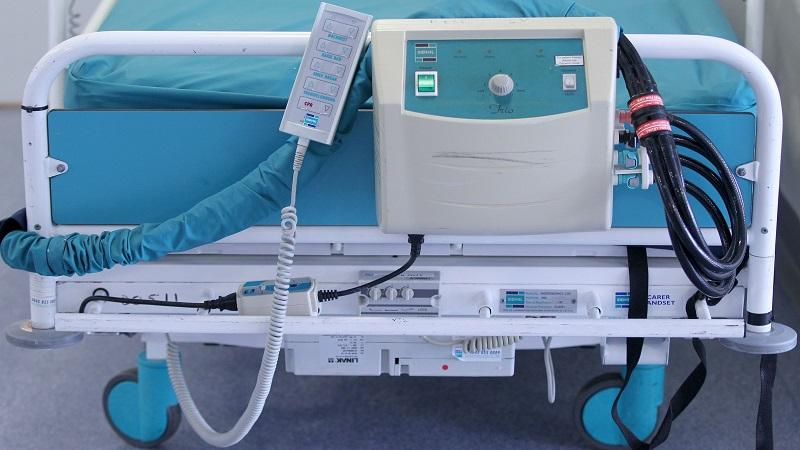 An image of the foot of an empty hospital bed