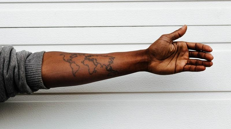 Image of a world map tattooed on a man's outstretched arm