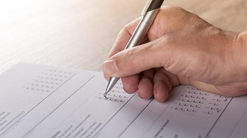 A close-up image of someone filling out a paper form containing a personality test