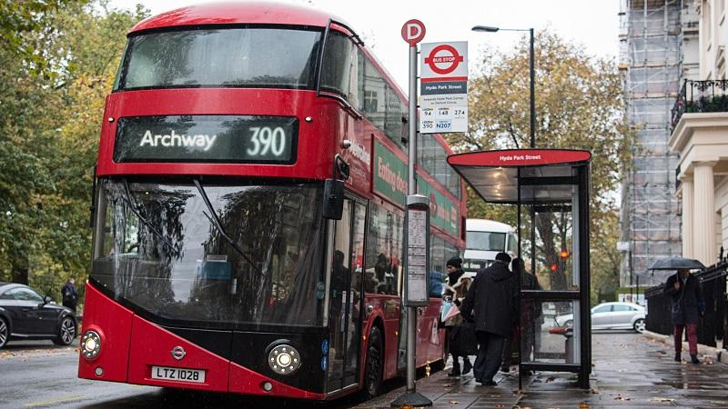 An image of a London bus admitting passengers at a bus stop