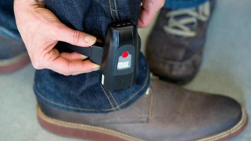 An image of an electronic tag being fitted to a man's ankle