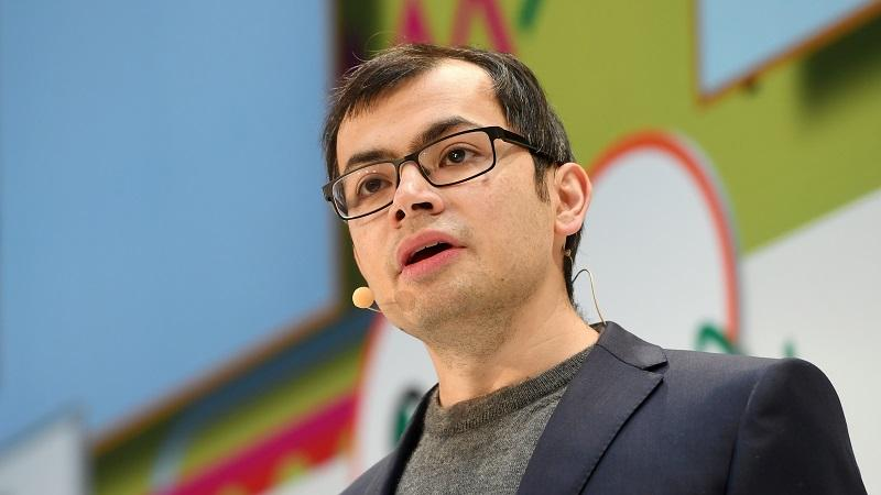 A close-up image of DeepMind CEO Demis Hassabis giving a presentation on stage